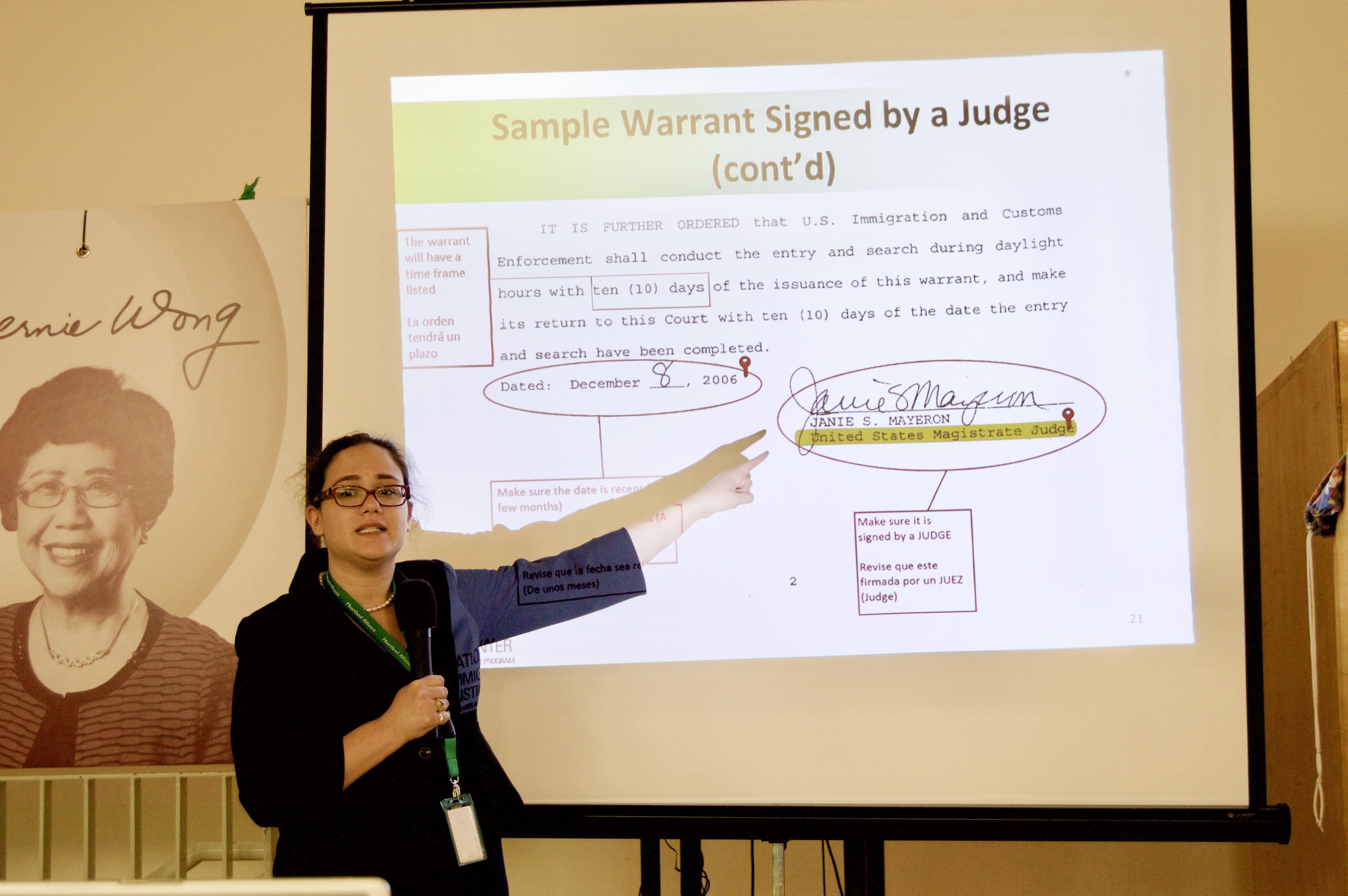 全美移民公義中心法務專員拉莫斯,向民眾展示含有效期限以及法官簽字的合法逮捕令樣本。(記者董宇/攝影)