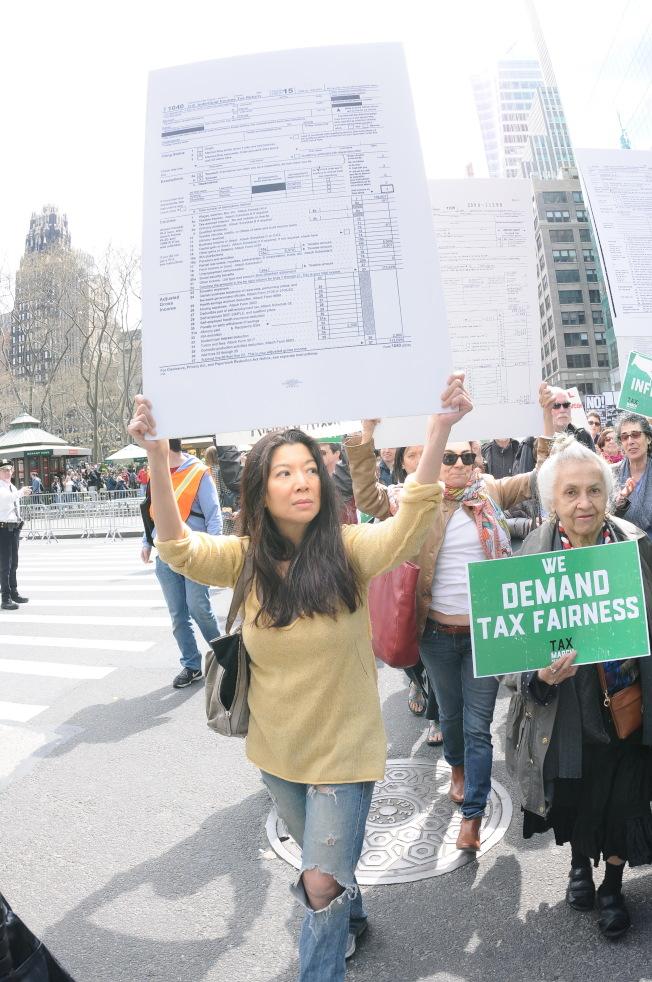 示威者高舉印有報稅表的牌子,要求川普公布稅表。(記者許振輝/攝影)