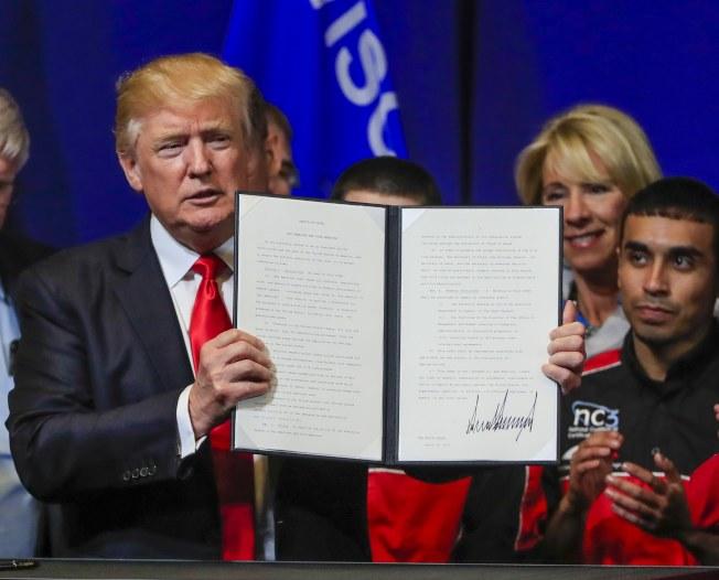 川普18日在威斯康辛州工人圍繞下,簽署行政命令,要求「買美國貨,雇美國人」。(歐新社)