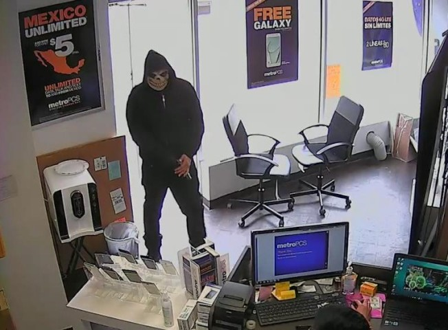 搶匪進店後,掏出一把手槍。(視頻截圖)