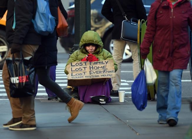 紐約市的貧富差距在過去10年逐漸擴大。圖為一名女遊民在曼哈頓街頭行乞。(Getty Images)