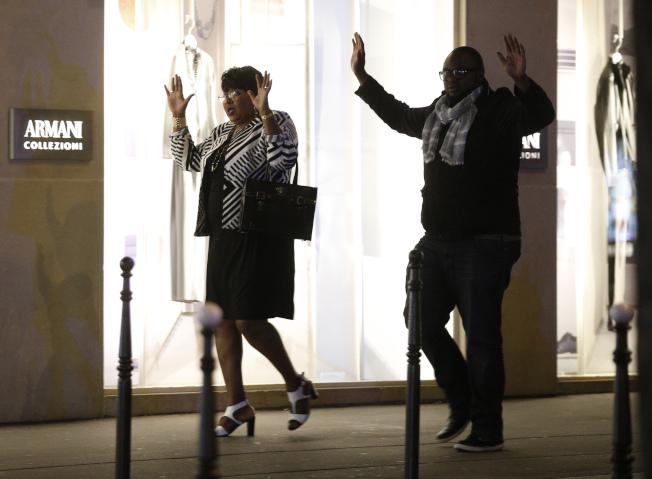 巴黎遭到恐襲,兩名路人高舉雙手走出封鎖區。(美聯社)