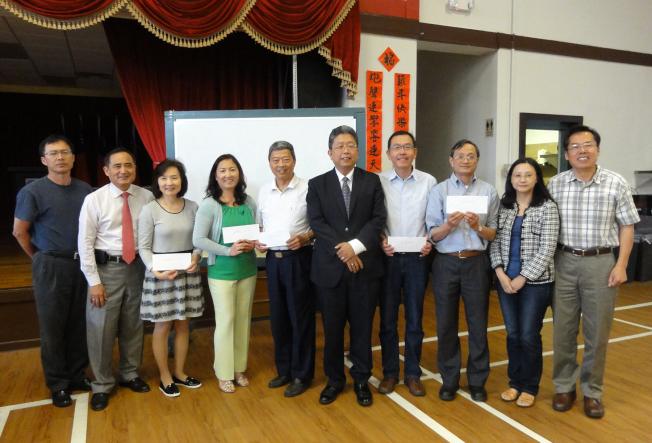 劉經巖(左六)在僑務座談會上頒發春節園遊會盈餘,給五所中文學校代表。(吳炳宏/攝影)