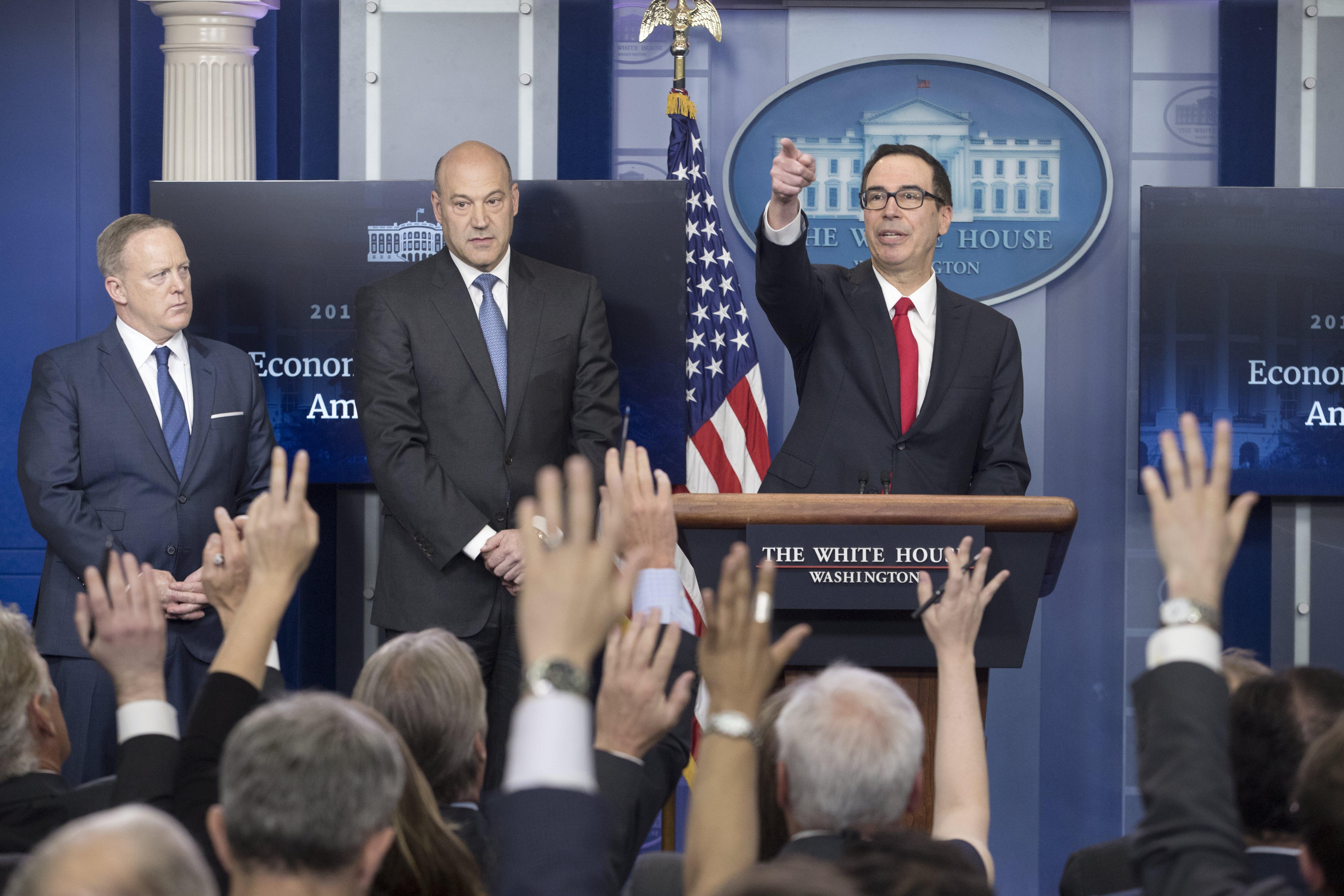 財政部長米努勤(右)與國家經濟會議主席柯恩(中)、白宮新聞秘書史派瑟舉行記者會,說明川普總統的減稅方案。(美聯社)