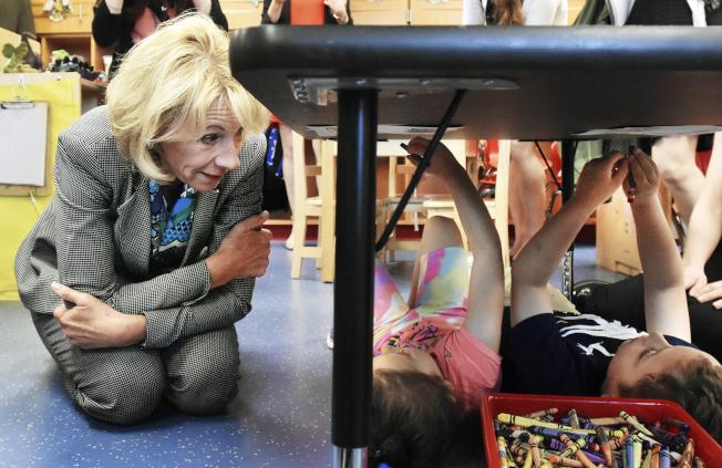 教育部長狄弗斯上周到俄亥俄州參觀一個幼兒園,與兩名五歲孩童交談。(美聯社)