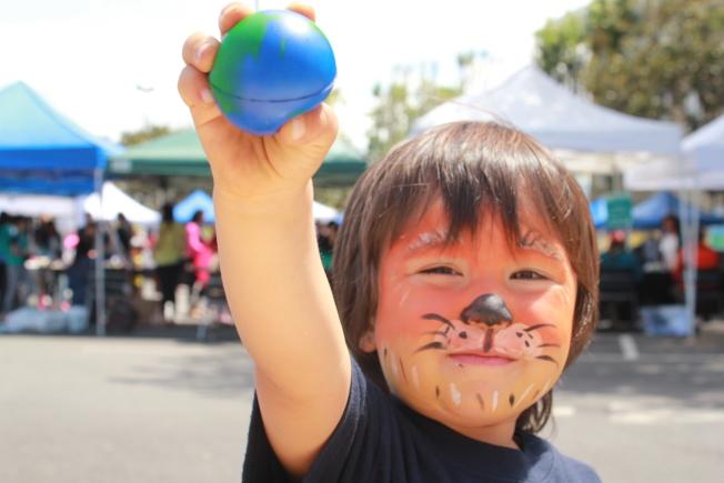 一名幼童上周參加地球日活動,舉起他的地球。(美聯社)