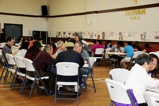 工作人員和義工一對一地為辦理公民入籍的人們,解說相關法律與辦理申請程序。(章慧娟/攝影)