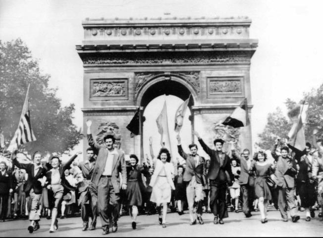 法國民眾1945年5月8日 在巴黎凱旋門遊行時揮舞著同盟國的國旗,慶祝二次世界大戰歐陸戰場結束。(美聯社)