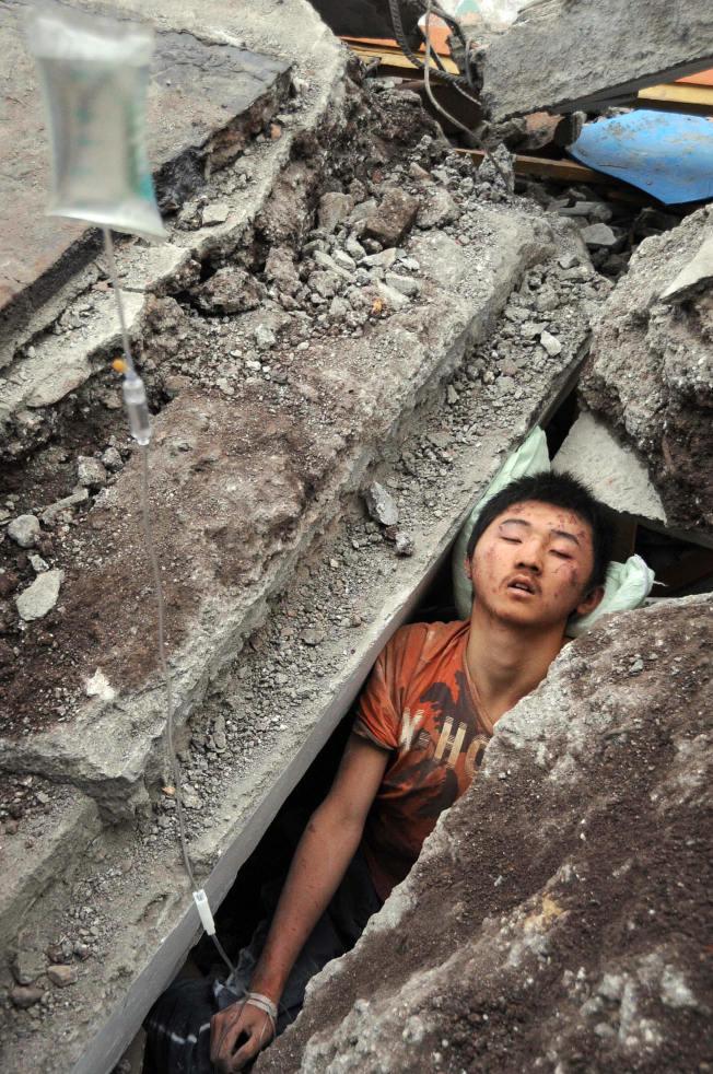 5月13日:一名男孩在廢墟中等待救援。(Getty Images)