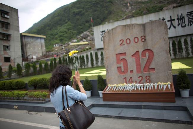 2013年4月24日,一名女士在北川地震紀念館石碑前祭拜。(Getty Images)