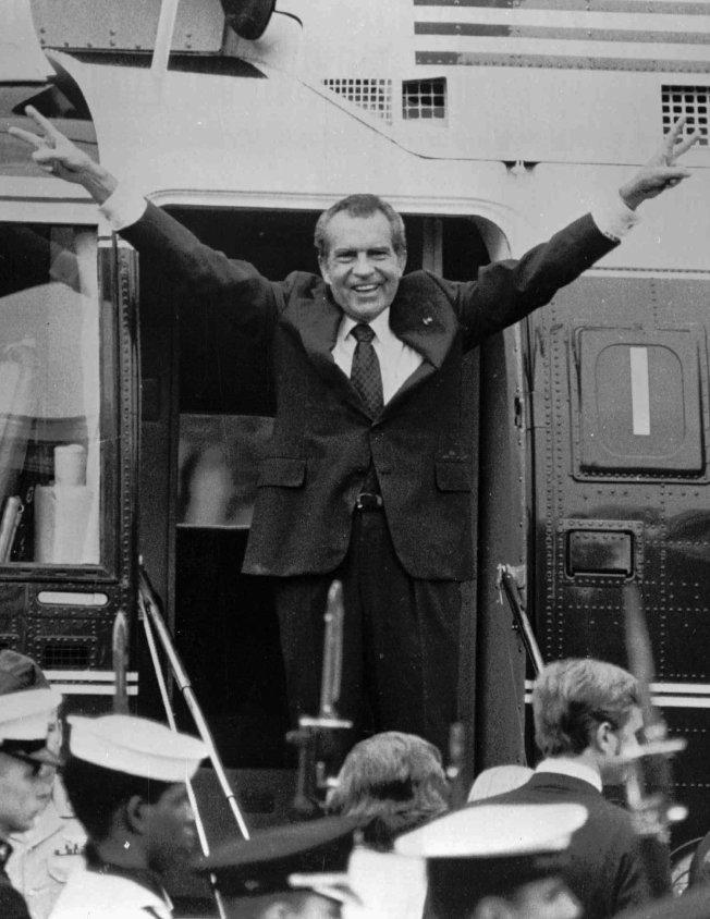 尼克森1974年8月9日在白宮草坪登上直昇機飛往安得魯斯空軍機場時,向白宮職員道別。(美聯社)
