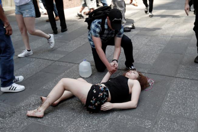 一名路人在安慰一名傷者。(路透)
