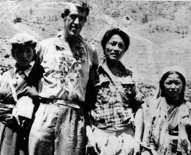 1953年6月19日,艾德蒙·希拉里 (左二) 與雪巴嚮導丹增·諾蓋 (右二) 成功攻頂後、在山下與當地居民拍照留念。(美聯社)