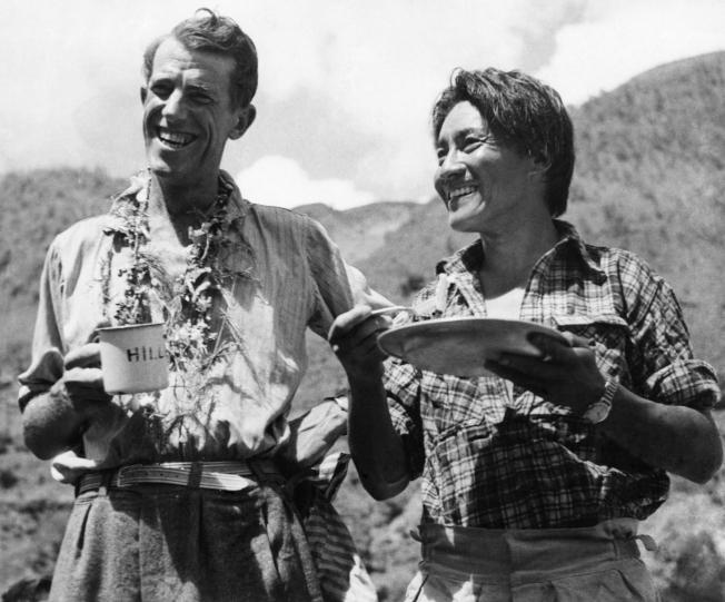 1953年6月19日,艾德蒙·希拉里 (左) 與雪巴嚮導丹增·諾蓋 (右) 攻頂聖母峰後、在山下享用早餐。(美聯社)