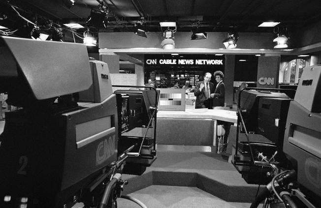 1980年5月31日,CNN時任總裁 Reese Schonfeld (左) 與女主播 Reynelda Nuse (右) 在新聞棚裡討論隔天開播事宜。(美聯社)