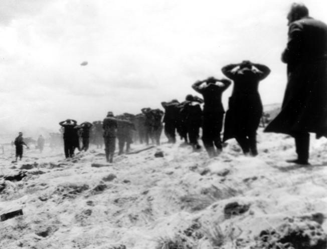 1944年6月6日,納粹戰俘在西歐盟軍的監管下,於法國猶他海灘 (Utah Beach) 排隊行走。(美聯社)