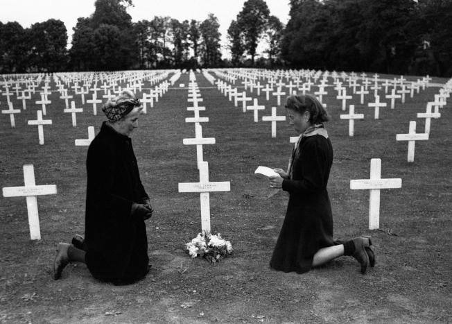 1945年6月6日,諾曼第登陸屆滿週年,兩名婦女於法國諾曼第海灘所設立的紀念墓園中,為戰爭犧牲者進行哀悼。(美聯社)