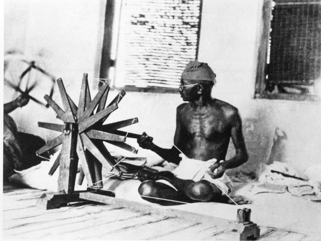 1931年,甘地用紡車紡紗自製衣服。(美聯社)
