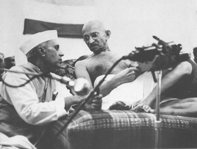 1942年8月8日,印度獨立運動領袖甘地 (右) 與一名印度議會代表談話 。(美聯社)