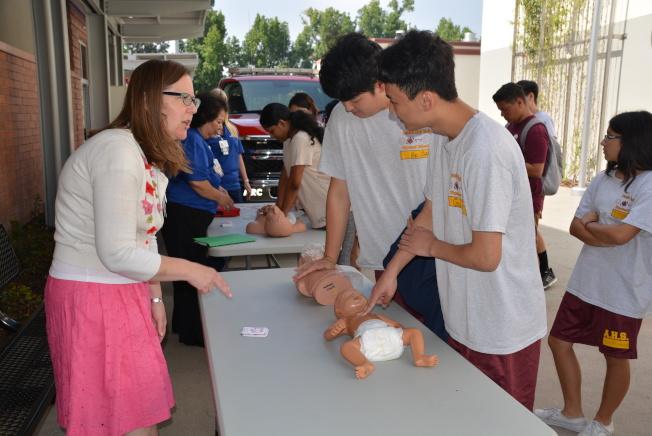 南加州衛理公會醫院人員(左)指導學生掌握心肺復甦施壓手法要領。(記者丁曙╱攝影)