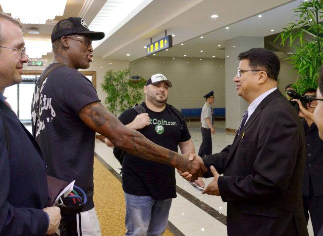 日本共同社提供的照片顯示,羅德曼(前左二)在平壤機場與送行的北韓官員握手。(路透)