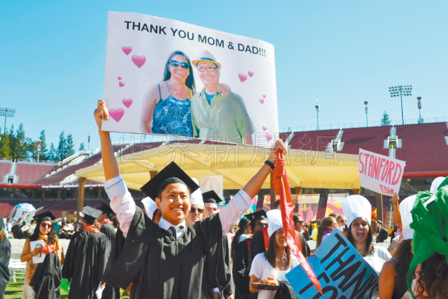 史丹福畢業生入場的趣味步行(wacky walk)活動上,學生高舉牌子表達對父母的感激。(記者張毓思/攝影)