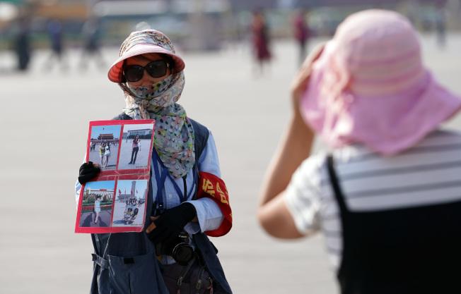 北京城區連日籠罩在高溫天氣中,18日最高氣溫超過攝氏40度。圖為天安門廣場的攝影師在酷熱高溫中向遊客拉生意。(中新社)
