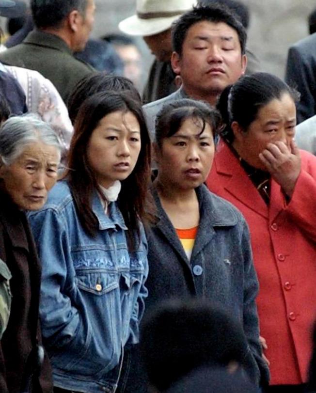 2002年6月20日,黑龍江雞西市成子河煤礦發生爆炸,111名礦工罹難。6月21日家屬焦慮等待搜救的消息。(美聯社)
