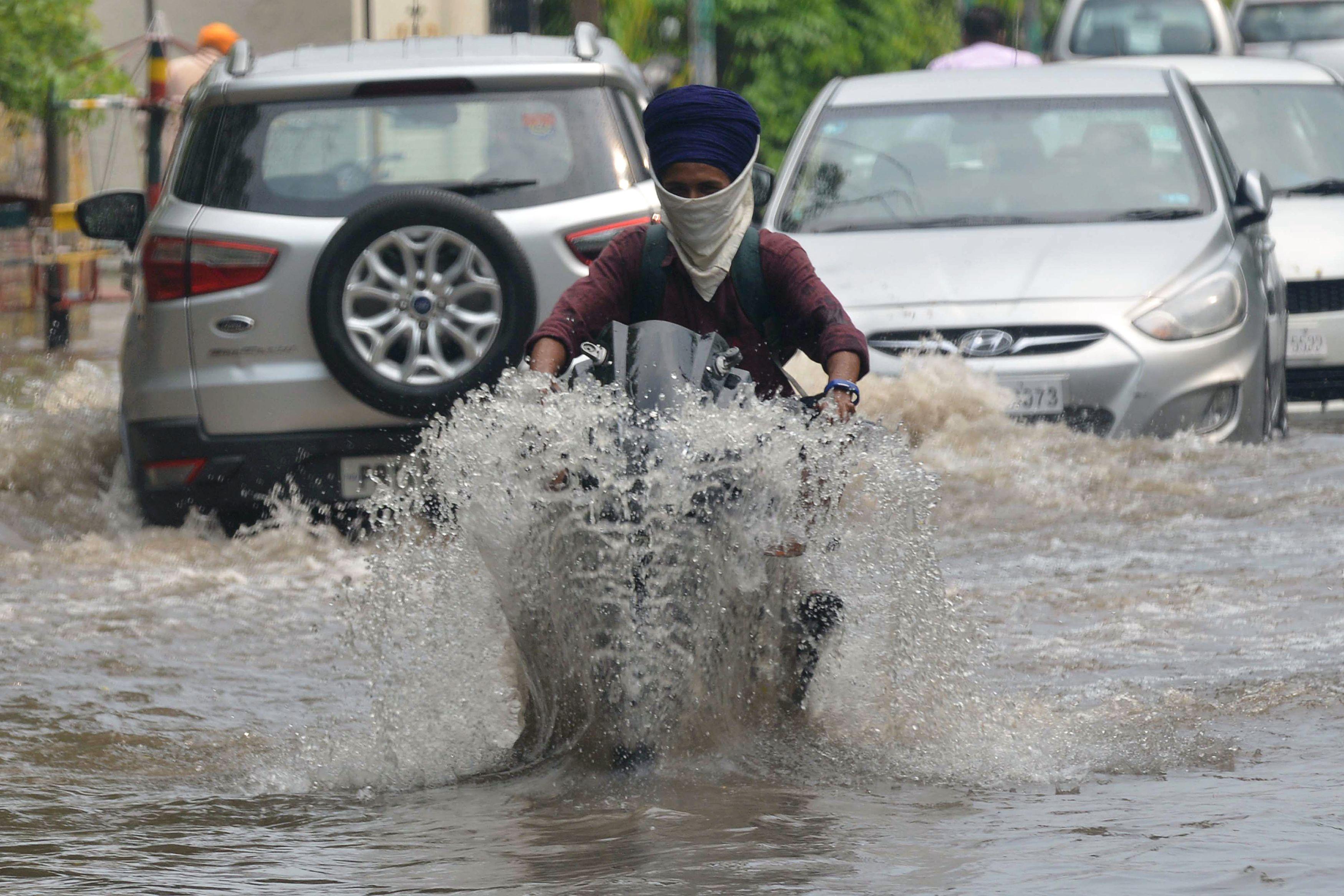 印度水災嚴重,民眾涉水而行。(Getty Images)