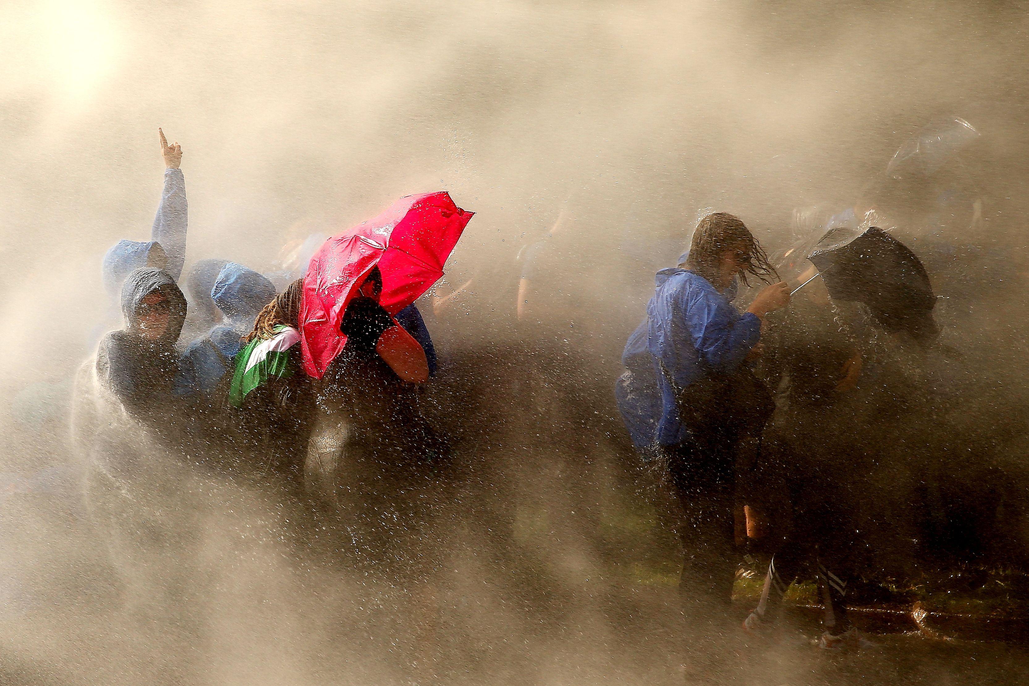 示威抗議者躲避鎮暴警察的水龍。(Getty Images)