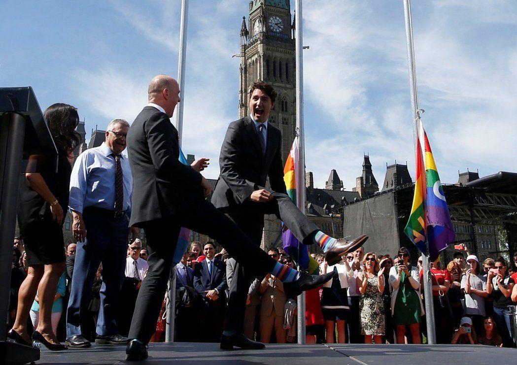 杜魯多(右)6月14日參加國會支持同性戀權利升旗活動,和國會議員一起展示彩虹襪。路透