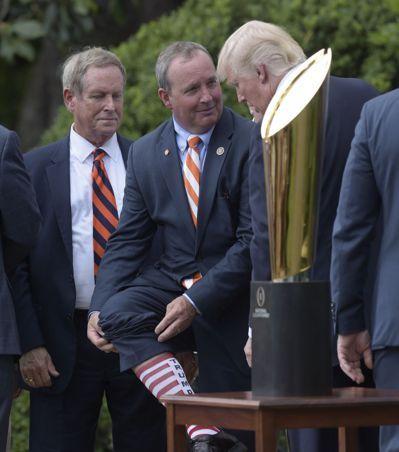 美國南卡州共和黨聯邦眾議員鄧肯(中)上月12日到白宮參加活動時,穿了一雙印有「川普」英文字樣的紅條紋襪子,還秀給川普總統(右)看。美聯社