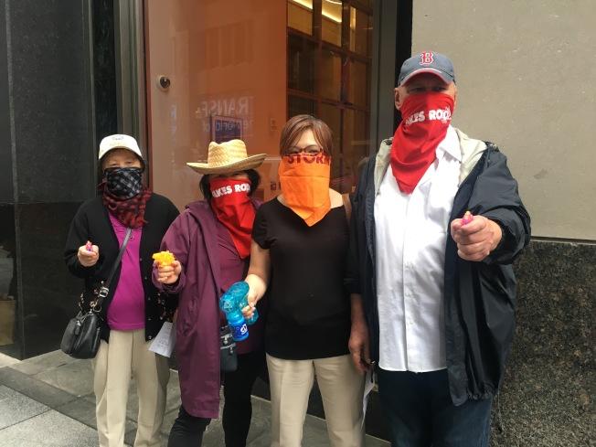 波士頓華埠公路村管理協會代表和支持組織代表以頭巾遮面、手拿水槍模仿電影中「公路搶劫(highway robbery)」的形象參與抗議。(記者劉晨懿之/攝影)