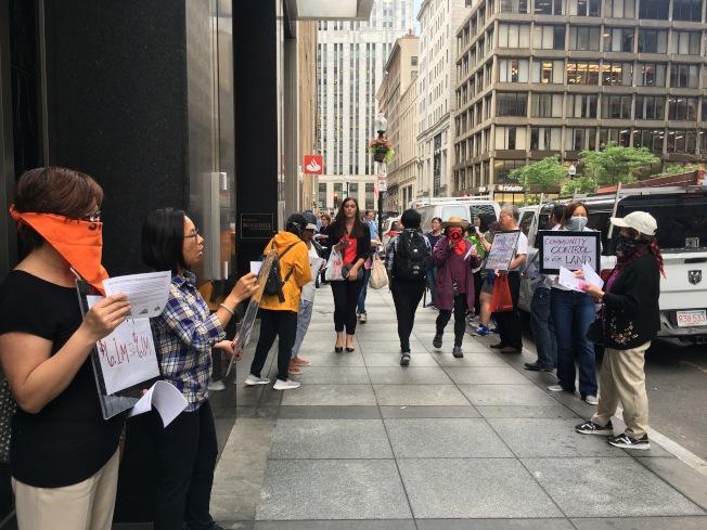 波士頓華埠公路村管理協會代表和支持者喊口號和發傳單抗議三一金融公司欲按市場價出售公路村物業給管理協會。(記者劉晨懿之/攝影)