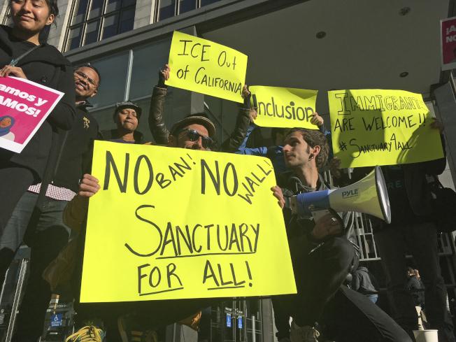反對遣返無證移民者在舊金山聯邦法院外面舉牌,要求收容無證移民。(美聯社)