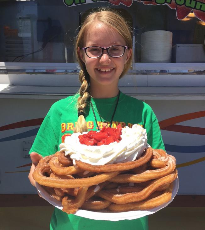 橙縣博覽會上,小女孩手裡拿著墨西哥油炸餅。(橙縣博覽會提供)
