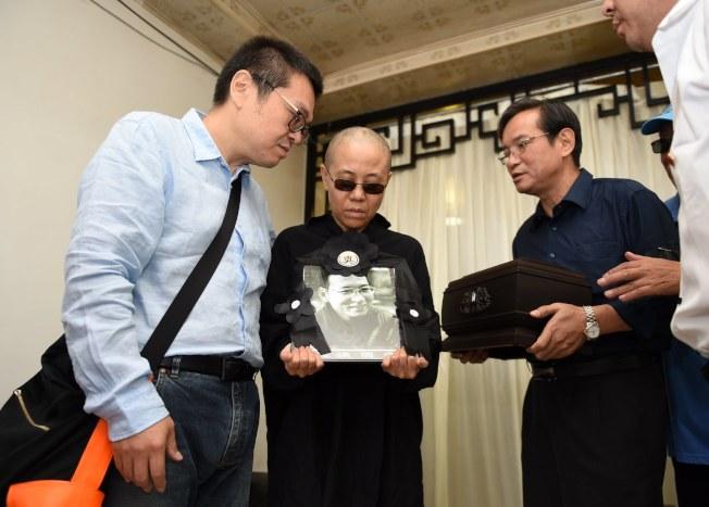 劉曉波的遺孀劉霞(中)捧著劉曉波的照片。(歐新社)