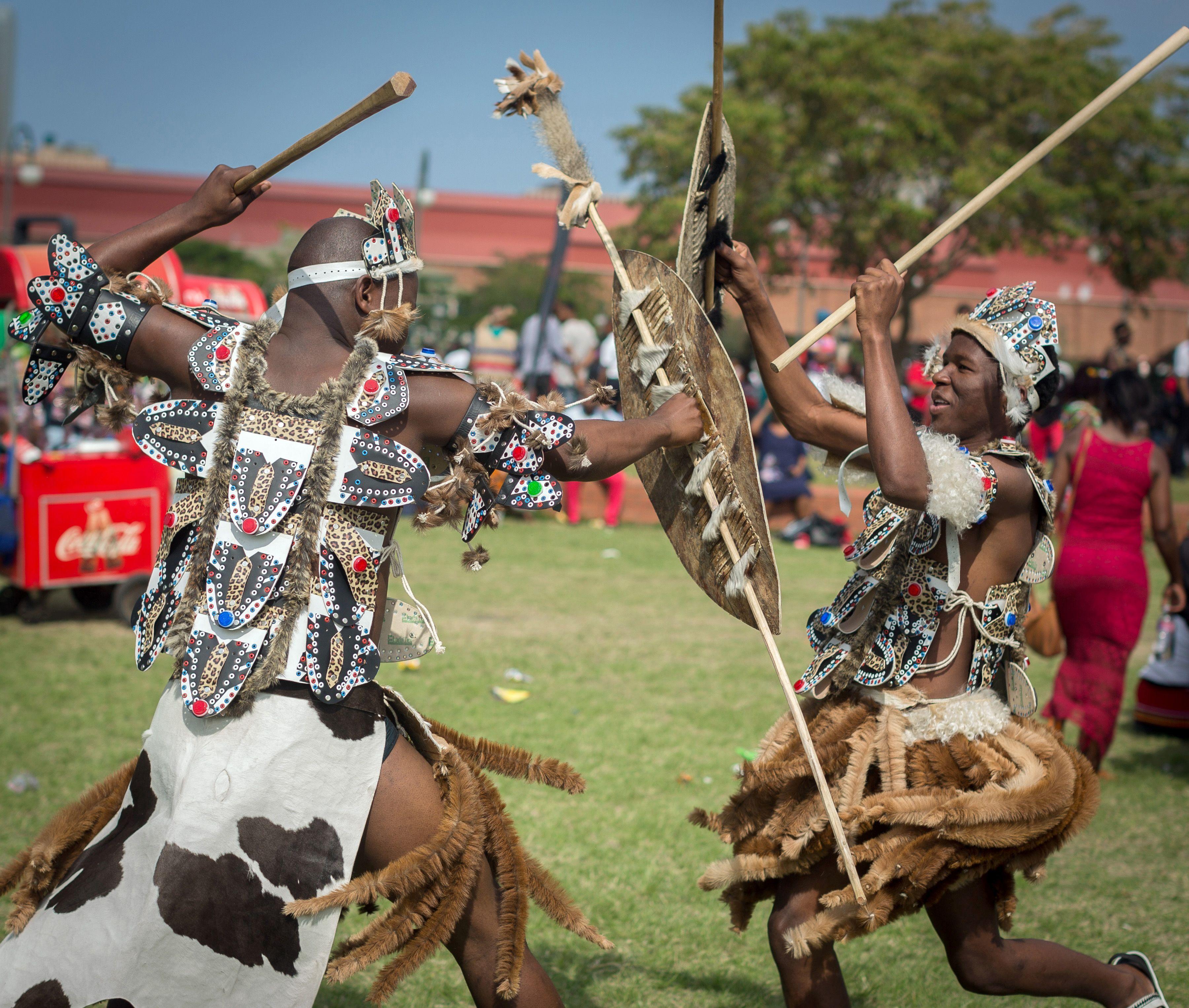兩位穿著南非祖魯族傳統服飾的男子表演戰鬥舞。(Getty Images)