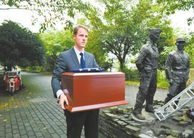 美方工作人員懷抱「駝峰航線」美軍骸骨盒,站在陳納德塑像旁。(中新社)