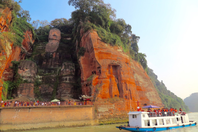 遊客乘船於岷江上觀樂山大佛。