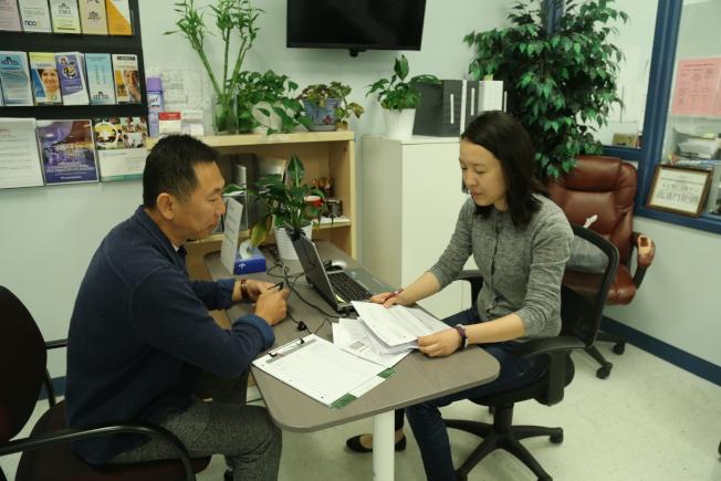 泛亞門診福利協調專員張凌(右),向前來諮詢的民眾介紹相關程序。(記者羅曉媛/攝影)