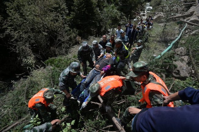 九寨溝地震後,武警救出一名重傷人員。(路透)