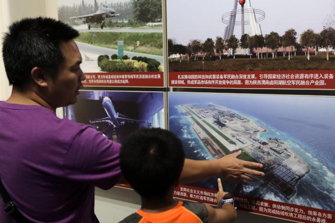 北京的軍事博物館裡展出中國在南海修築的人工礁照片。(美聯社)