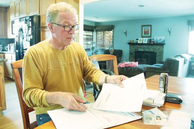 戴納德向記者展示自己為女兒申請綠卡和國籍的種種文書材料。(記者李晗/攝影)