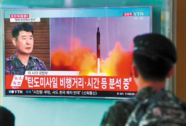 一名南韓士兵7月4日看電視新聞播出北韓發射飛彈的影片。(Getty Images)