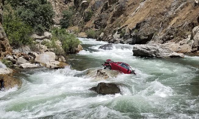 兩名泰國留美交換學生的紅車墜落崖下急流,剛好卡在岩石上面。(美聯社/佛瑞斯諾縣警局提供)