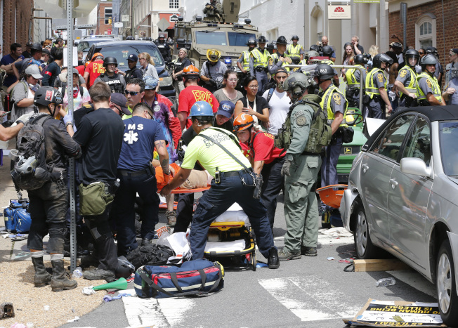 汽車衝入人群造成大量死傷後,援救人員在現場展開急救。(美聯社)