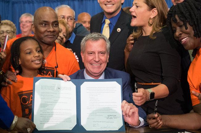 白思豪11日簽署通過第214-B法案,低收入戶家庭在面對驅逐訴訟時只要撥打311就能夠獲得免費的律師代表。(市長辦公室提供)