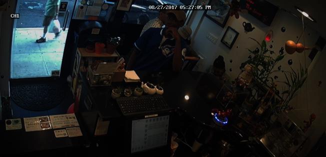 穿藍色上衣的非洲裔男子,在入店行搶前曾先來了解店內情況。(店主視頻截圖)