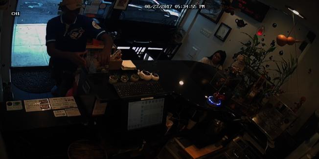 穿藍色上衣的非洲裔男子進店企圖搶走台子上的透明塑料小費盒。(店主視頻截圖)